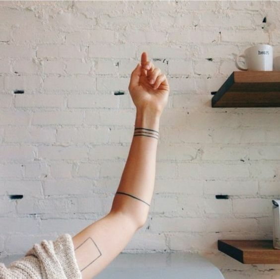 Exemple tatouage minimaliste bracelet lignes tribales avant bras femme