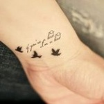 photo tattoo feminin poignet phrase et hirondelles