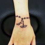 tatouage feminin bracelet chapelet avec ailes