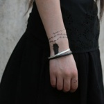 tatouage feminin bracelet chapelet perles avec pendentif plume sur 3 tours