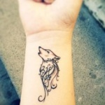 tatouage femme interieur poignet tete de loup et arabesques
