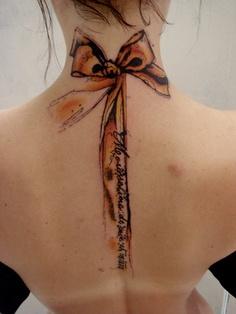 tatouage phrase fille sur la colonne vertebrale avec un long noeud tatoue