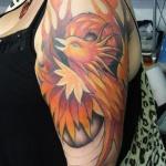 phoenix tatouage femme sur la surface du bras et epaule avec flammes