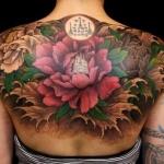 photo magnifique tatouage fleur de lotus femme moitie du dos et epaules