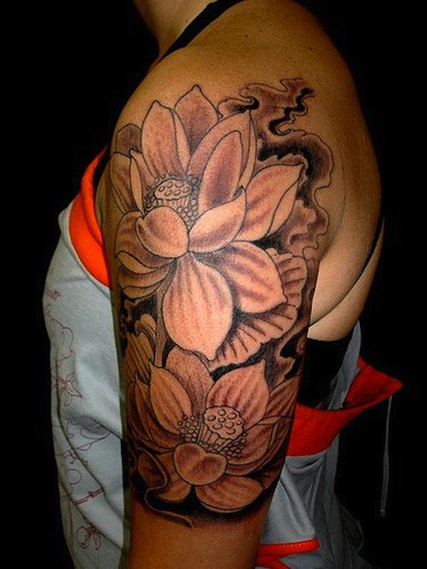 photo tatouage fleur de lotus femme epaule et bras encre noire