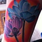 tatouage femme fleur de lotus bleu et violet mollet