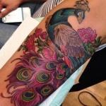 beau tattoo feminin paon avec ses plumes et fleurs cuisse