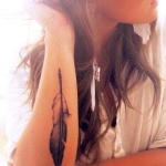 plume femme a tatouer le long du bras