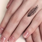 tatouage doigt annulaire bijou plume fille