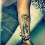 tatouage femme 2 plumes dans attrape reve interieur bras