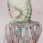 tatouage femme dos recouvert de plumes indiennes
