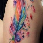 tatouage symboles plume oiseaux haut de cuisse fille style aquarelle