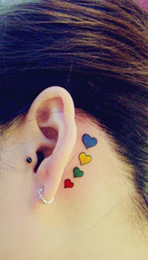 exemple tatouage 4 coeurs bleu jaune vert et rouge femme derriere oreille
