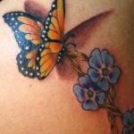 photo tattoo 3d feminin papillon monarque butinant une fleur