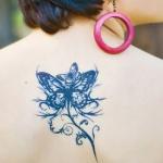 tatouage femme 2 papillons sous nuque haut du dos au bout d une tige de fleur