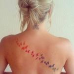 tatouage femme nuee de papillons dans le dos degrade orange rose bleu vert