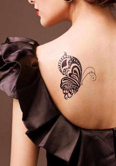 tatouage femme papillon tribal de profil omoplate