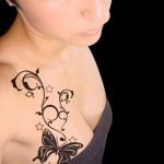 tatouage symbole papillon noir fille sur haut du sein et clavicule
