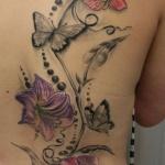 dos tatouage femme orchidees et papillons moitie droite
