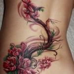 tatouage femme bas du dos et cote dessus fesses fleurs et branches