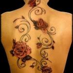tatouage femme nuque et dos avec roses rouges et arabesques