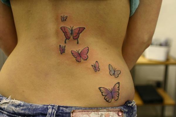 tatouage symboles papillon bas du dos fille  cote droit