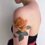 photo tattoo feminin rose jaune orange sur haut du bras