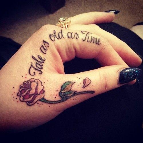 tatouage femme rose main avec petale qui tombe et phrase sur doigt index