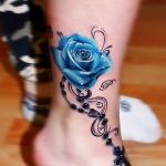 tatouage rose bleu femme avec chapelet et croix sur cheville