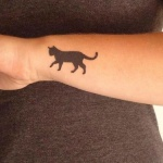 Photo tattoo feminin chat noir marchant sur le poignet