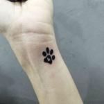Tatouage symbole empreinte chat avec coeur au centre sur poignet