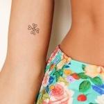 Tatouage femme discret haut du bras interieur 4 coeurs formant une croix