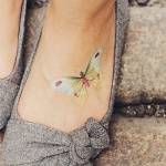 Petit tatouage femme papillon en couleur sur pied