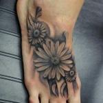 Photo tattoo feminin pied trois fleurs avec belles ombres