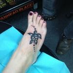 Photo tattoo femme maori tortue pied