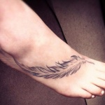 Tatouage pied fille longue plume noire en diagonale
