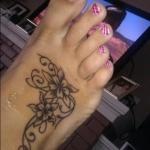 Tatouage symboles fleurs arabesques devant pied fille