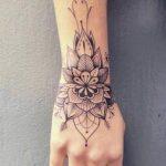 Mandala fin fleurs tatoue sur main et poignet