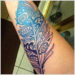 Tatouage mandala plume encre noire et bleu pour bras femme
