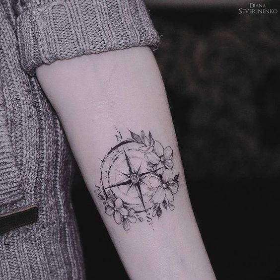 Idee tattoo bras boussole entouree de fleurs