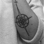 Photo tattoo feminin rose des vents en direction du mot family