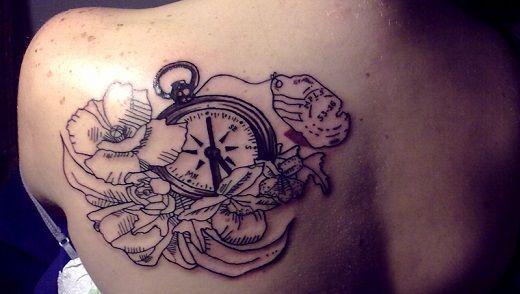 Tatouage boussole montre gousset femme entourees de fleurs haut du dos omoplate