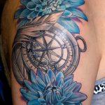 Tatouage bras et epaule femme boussole compas marine avec plume et chrysanthemes bleues