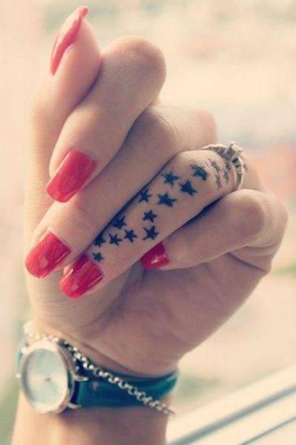 Exemple tatouage doigt annulaire recouvert de petites etoiles noires