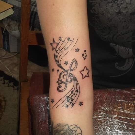 Photo tattoo portee musicale avec notes de musiques et etoile avant bras
