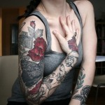 tatouage manchette feminin rouge et noir fleurs et insectes